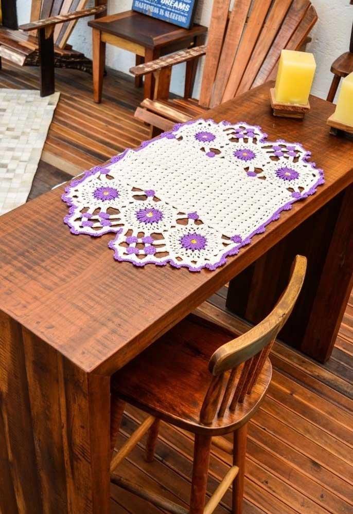 A cor lilás combina muito bem com a branca e o efeito desse centro de mesa de crochê fica incrível na mesa de madeira.