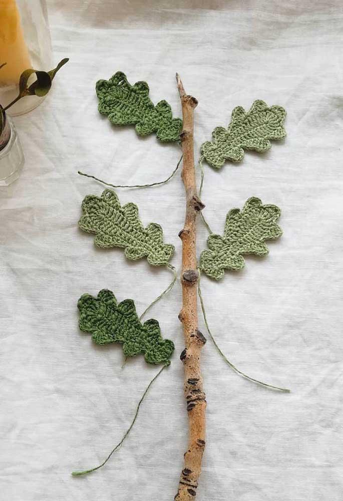 Se a intenção é fazer algo mais natural, pegue um pedaço de galho de árvore e cole as folhas de crochê nele.