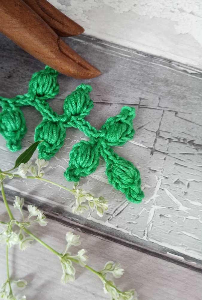 Um galho com folhas naturais ao lado de folhas de crochê.
