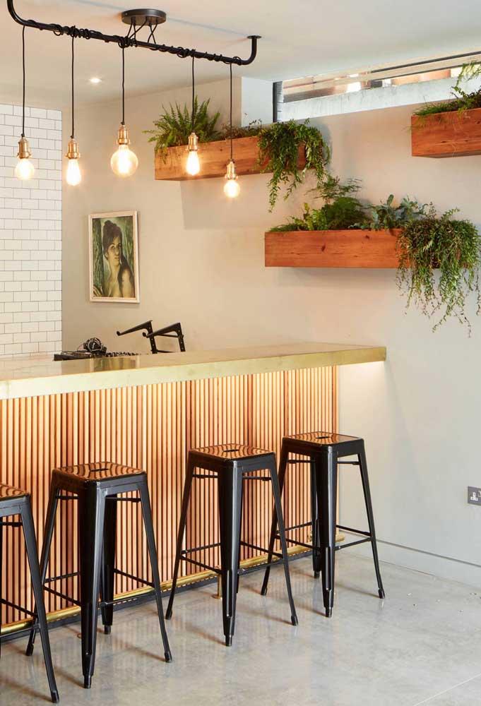 No bar da casa, as caixas de madeira acomodam as plantas em um discreto e charmoso jardim vertical