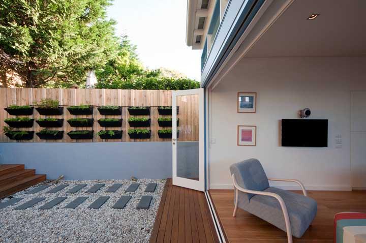 Os vasos pretos do jardim se destacam frente a cerca de madeira clara