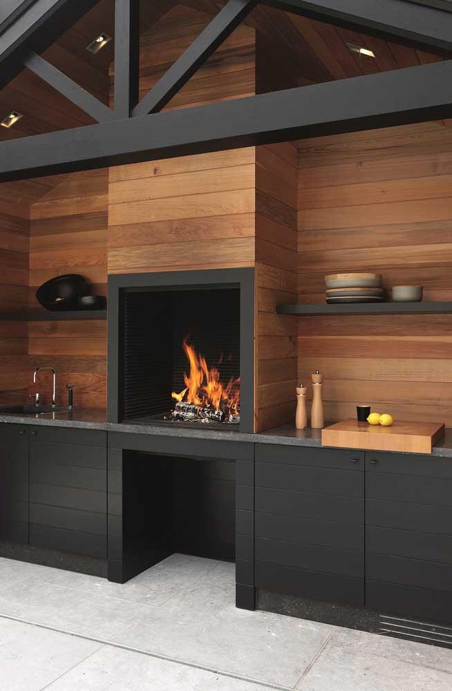 Essa é para se apaixonar! O revestimento de madeira combinado com a cor preta deixou a churrasqueira incrivelmente bonita