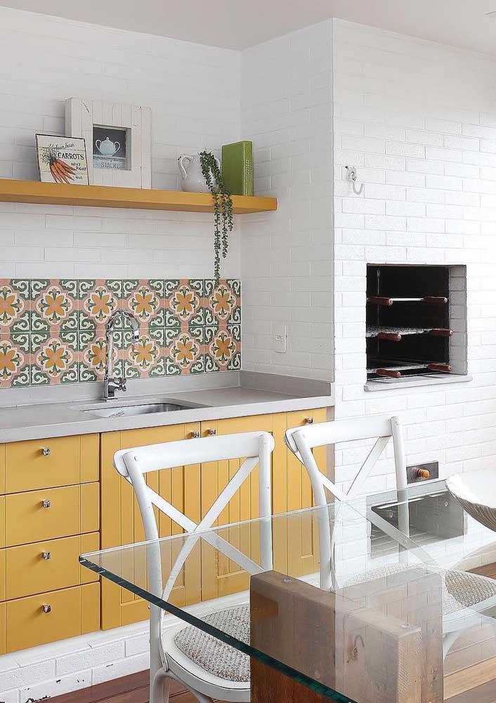 A área externa retrô apostou no uso de uma churrasqueira de tijolinhos brancos