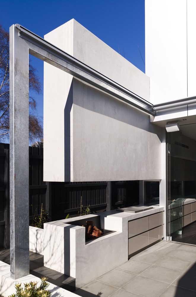 Sob a luz do sol, a churrasqueira de chão acompanha o visual moderno da casa