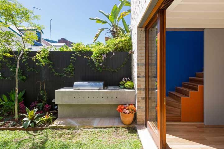 Sobre a bancada de concreto aparente e emoldurada pelo verde das plantas, se destaca a estrela do churrasco