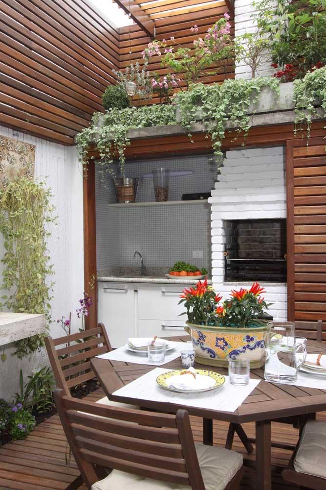 Aqui, a churrasqueira de tijolinhos foi pintada de branca o que ajudou a destacar a madeira usada na área externa