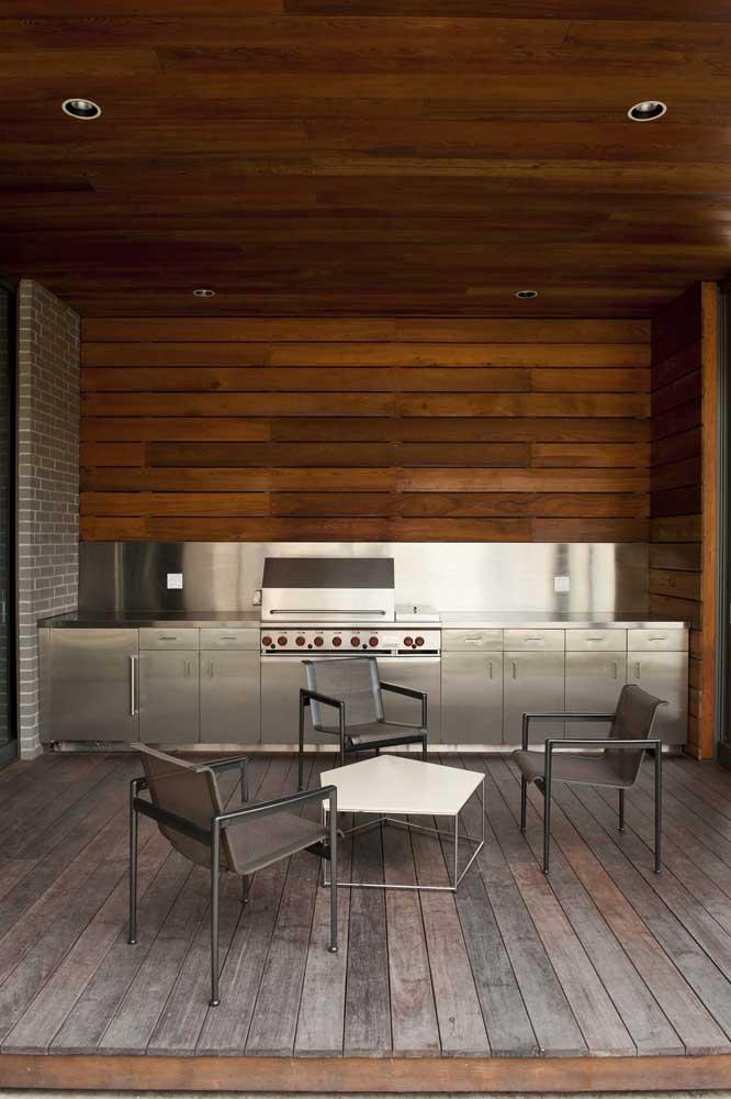 Entre o rústico e o moderno: essa área externa combina madeira e aço inox com harmonia; entre os dois materiais aparece a churrasqueira a gás