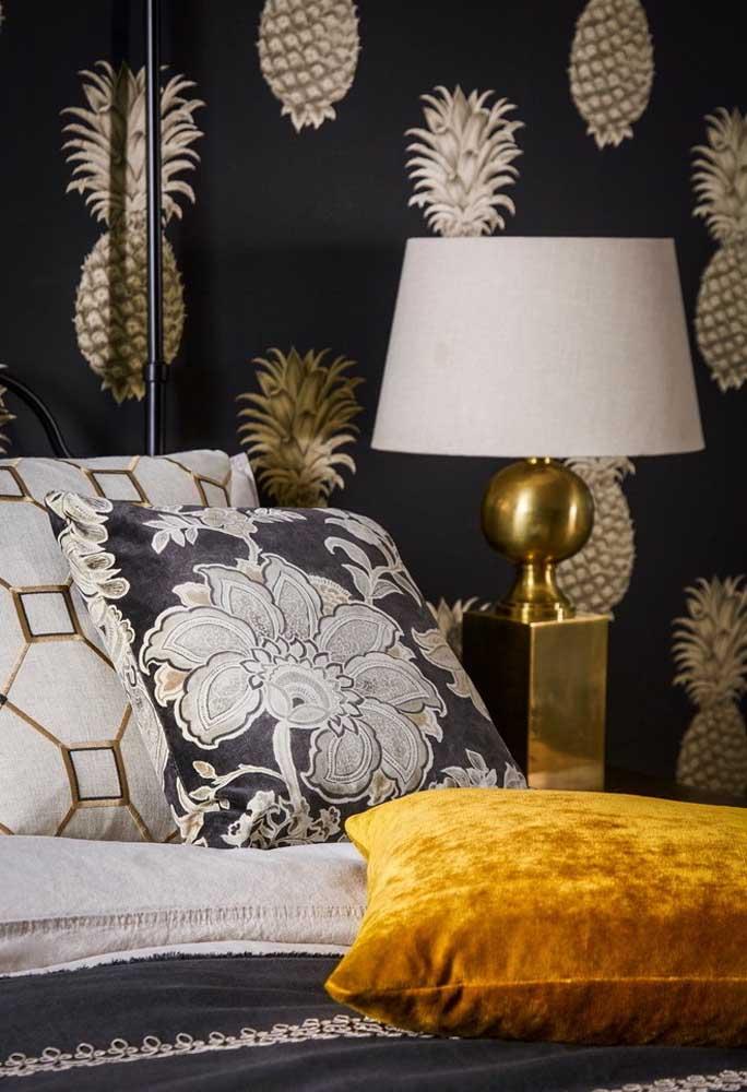 Quem disse que um quarto preto não pode ser luxuoso? O desenho do abacaxi nos tons dourado, o detalhe dourado do abajur e as peças escolhidas para o conjunto de cama fizeram toda a diferença.