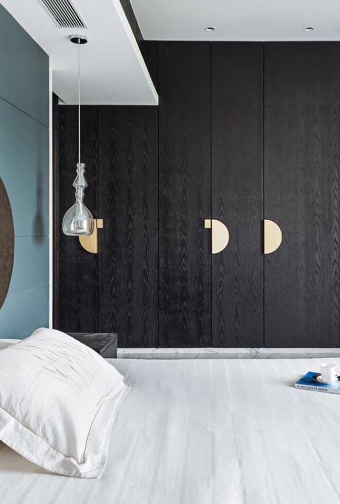 Ao invés de usar a parede na cor preta, aposte no armário que preenche o quarto todo.