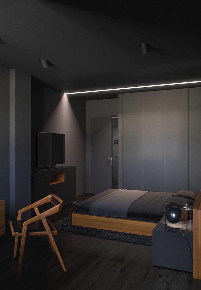 O contraste dos móveis de madeira em um quarto preto, faz com que o ambiente fique mais leve.