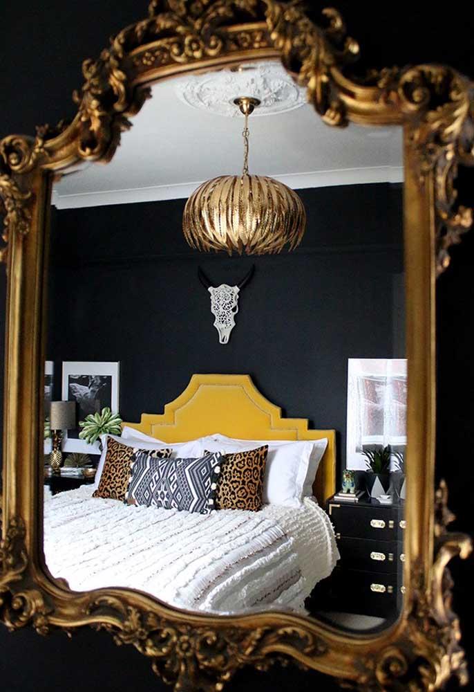 Um espelho com moldura dourada é o suficiente para destacar uma parede na cor preta.