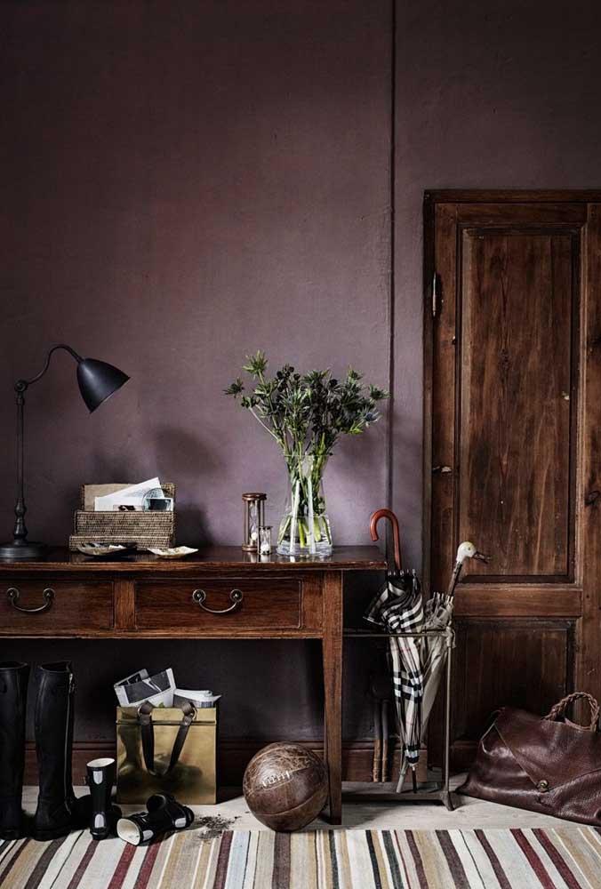 A cor vinho usada na parede dessa sala combinou perfeitamente com a porta e a mesa de madeira bem velha.