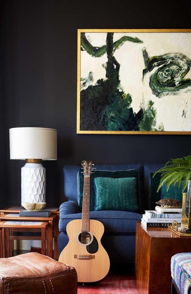 Uma parede na cor escura combina com os móveis de madeira. Para destacá-la, aposte em um quadro diferenciado.