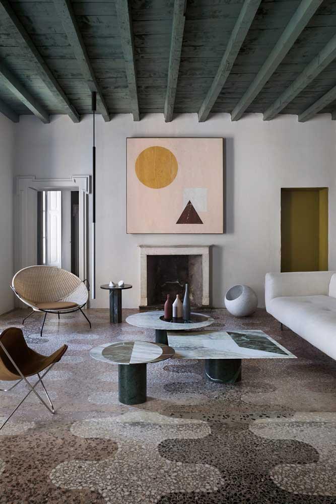 Apesar do teto ser feito de madeira, o modelo do piso deixou a sala com um visual totalmente moderno, principalmente, com a combinação dos móveis com design geométrico.