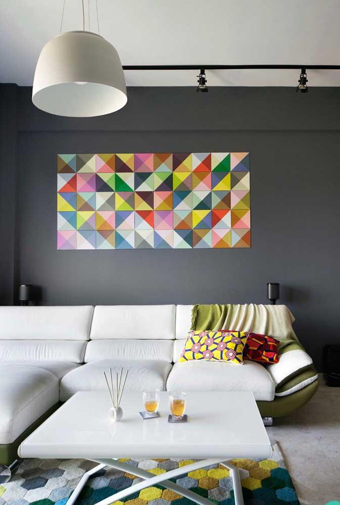 O quadro feito de mosaico colorido fica perfeito com a cor cinza da parede, assim como o tapete colorido fica ótima com o piso claro.