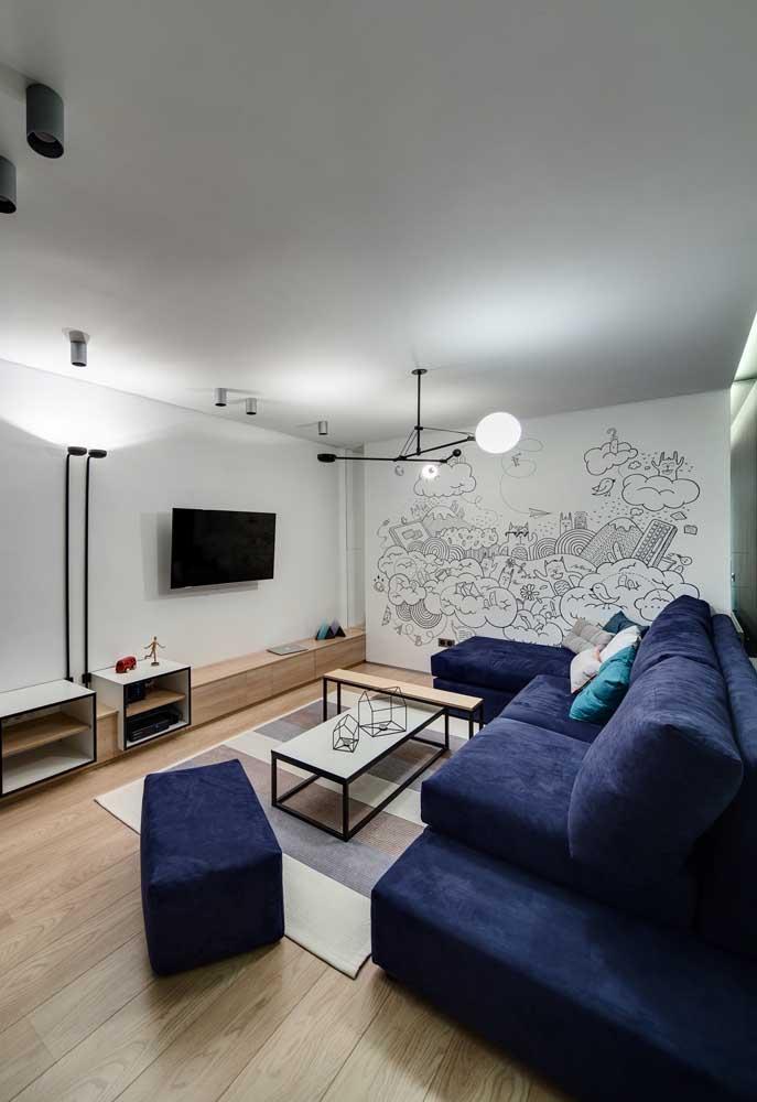 Para dar mais vida à uma parede totalmente branca, contrate um profissional que trabalhe com desenhos e destaque a parede da sala dessa forma.