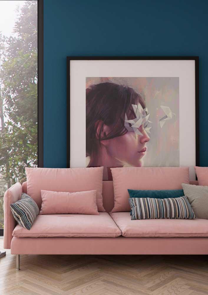 Para combinar com a parede na cor azul escuro, invista em um sofá no tom rosa claro.