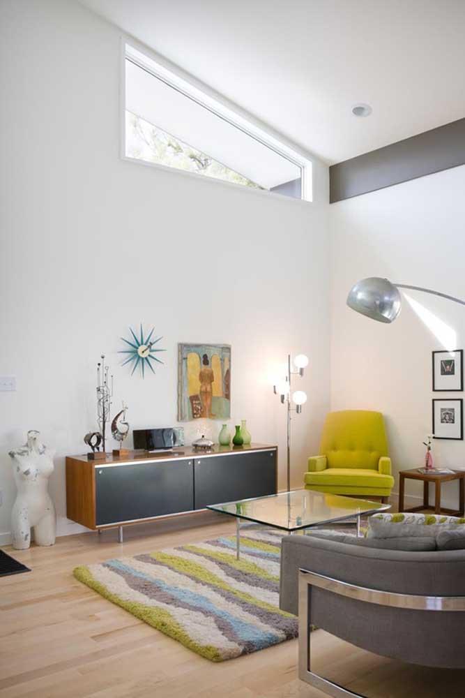 O sofá na cor verde limão e o tapete nas cores cinza e verde limão combinaram muito bem com as cores da parede e do restante dos móveis.