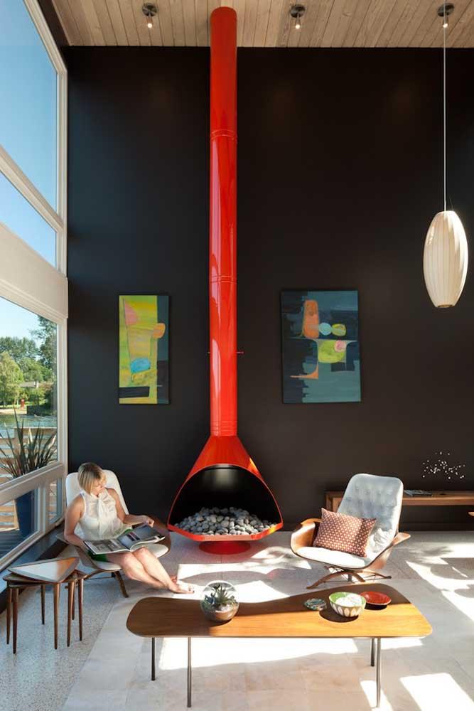A cor vermelha por ser um tom mais quente e que chama bastante atenção, pode ser usada em algum objeto decorativo, como é o caso dessa lareira feita de ferro que fica centralizada na sala.
