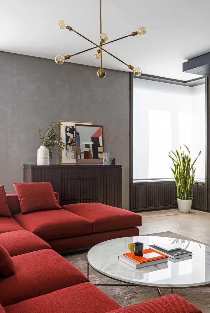 Que tal pintar a parede da sala no tom de cinza que mais parece cimento queimado? Para completar a decoração, escolha um sofá na cor vermelha.
