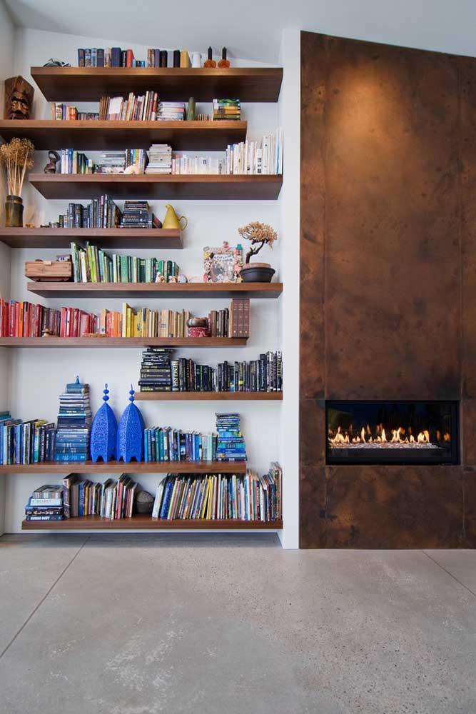 Os nichos de madeira seguem a mesma cor da textura pintada na parede, deixando o ambiente mais charmoso.