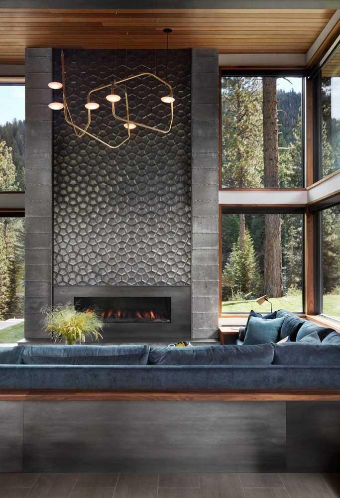 A textura usada na parede que leva a lareira é o grande destaque da decoração da sala.