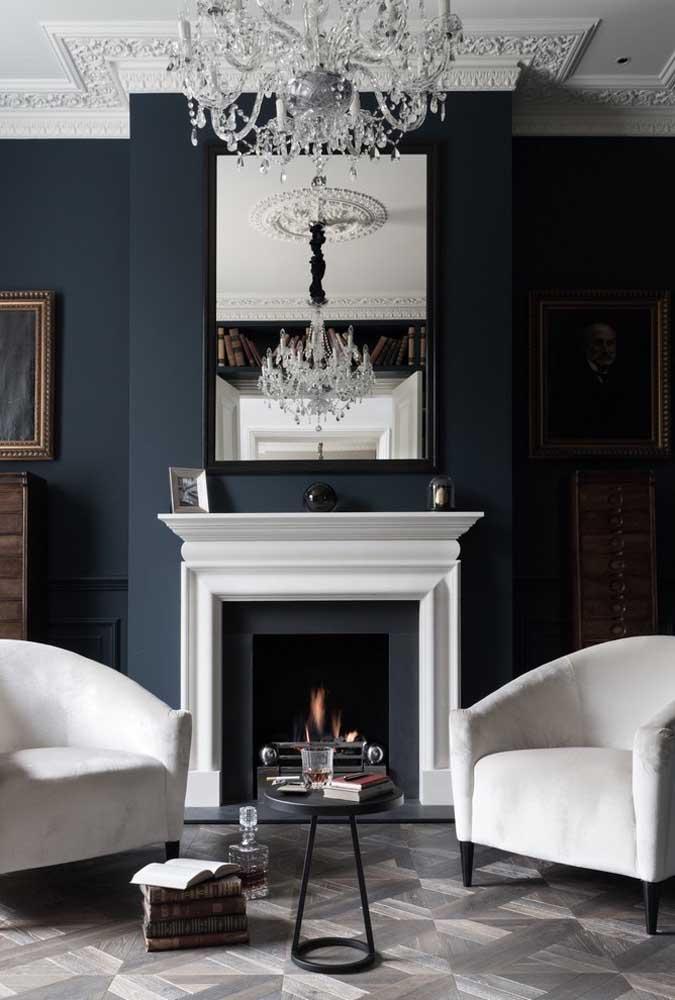 A mesma coisa acontece aqui, mas nesse caso é a cor azul com os detalhes em branco que deixaram a sala muito mais sofisticada. O espelho na parede da lareira junto com o luxuoso lustre dá o toque final.