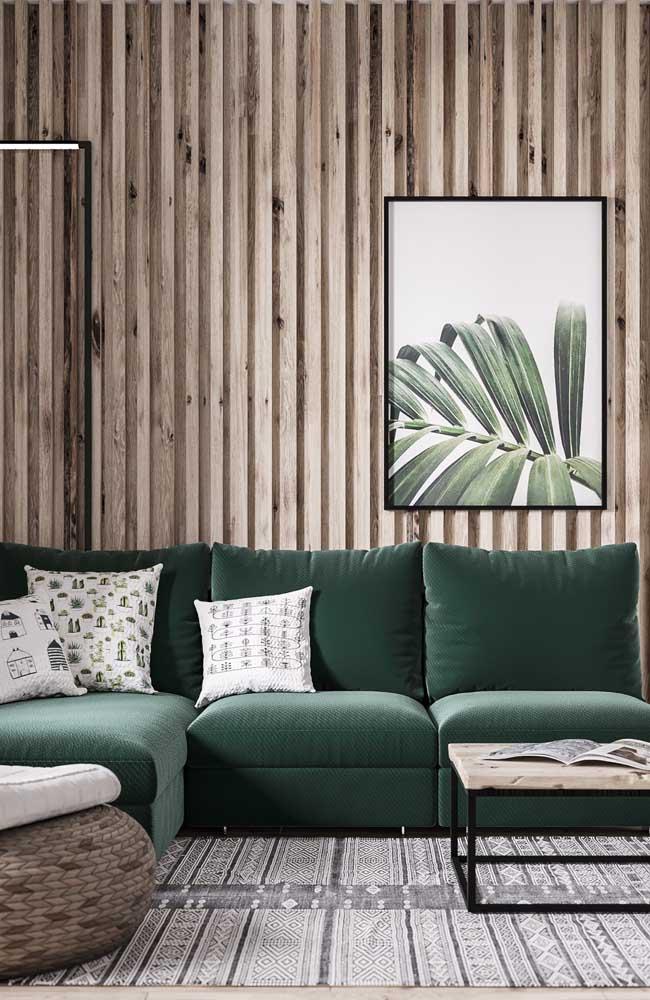 Ao invés de pintar a parede, que tal usar uma textura com aparência de madeira? O sofá no tom verde e o quadro com a foto da folha fecham toda a decoração.