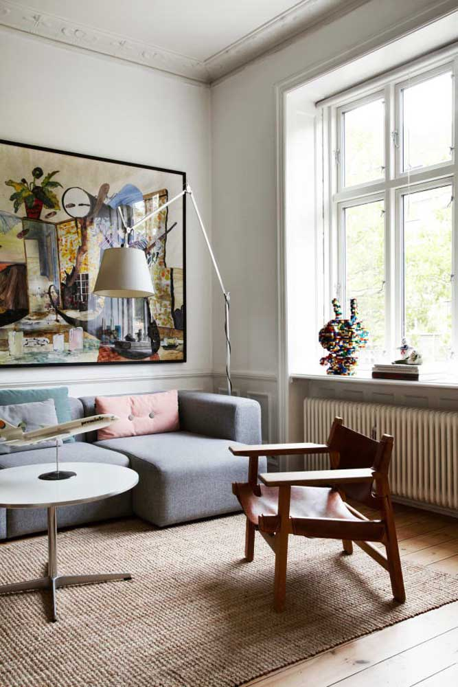 Para deixar a sala com uma decoração mais rústica, aposte no piso de madeira e por cima um tapete de palha.
