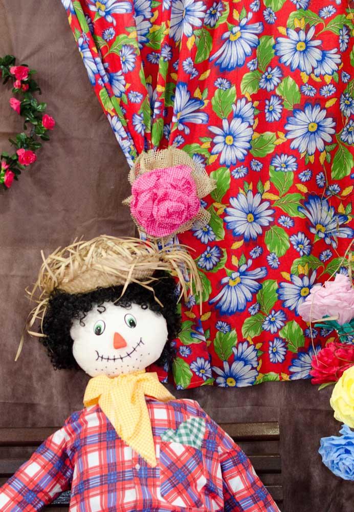 Se a intenção é fazer uma decoração mais simples, pendure um tecido estampado, decore com flores e coloque um espantalho para receber os convidados.