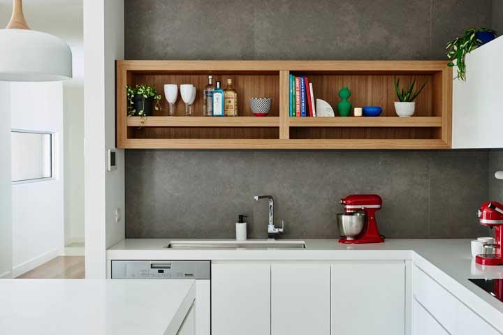 Um nicho de madeira fica perfeito na parede de cimento.