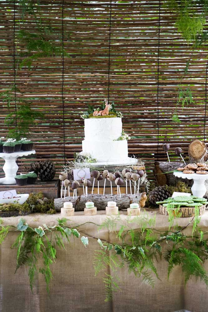 Coloque alguns troncos e galhos na decoração da mesa principal da festa para deixar a mesa com uma aparência de floresta.