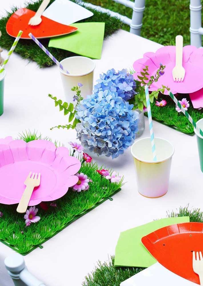 Substitua o jogo americano por um feito com gramas e flores artificiais, lembrando um belo jardim.