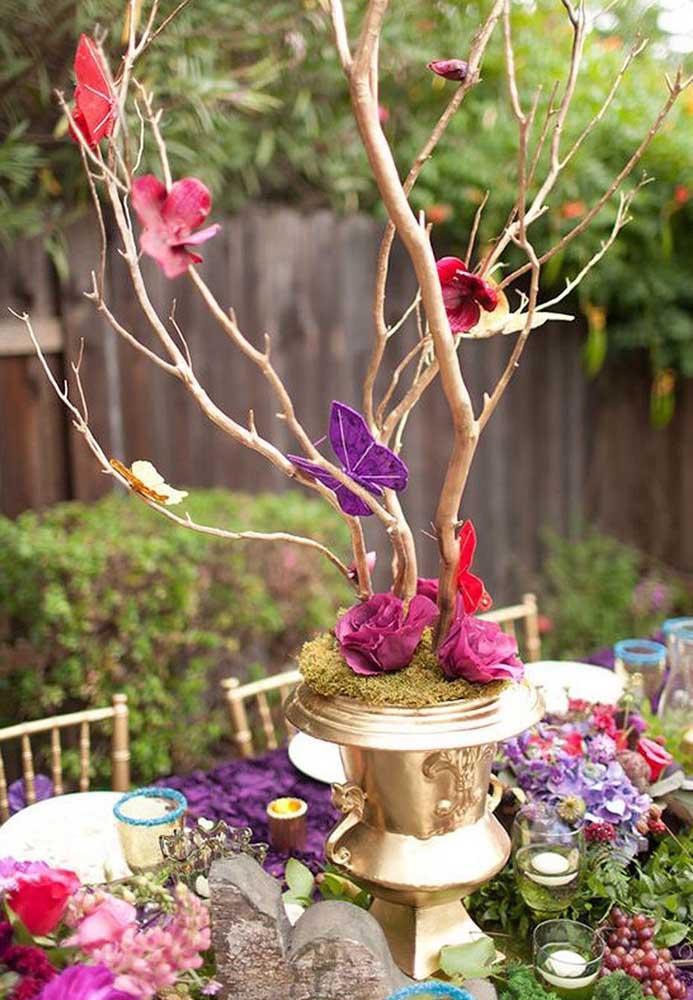 Ou aposte em um galho seco para decorar com alguns elementos que fazem referência ao tema Jardim Encantado.