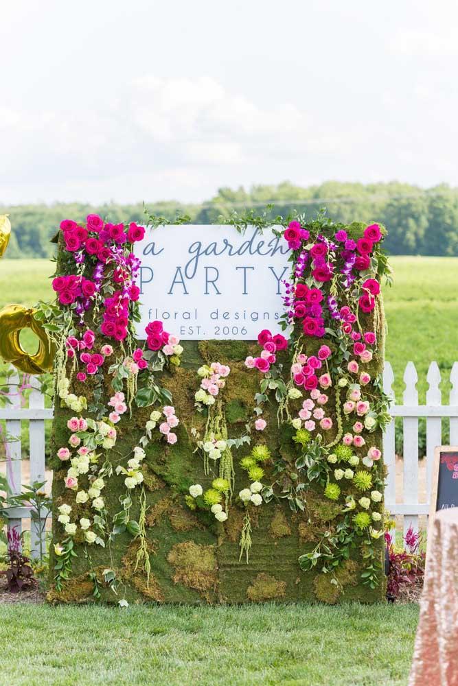 Painel feito de blocos de grama e muitas flores para informar sobre a festa Jardim Encantado.