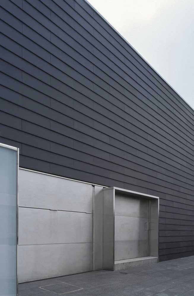 O portão de aço prateado é o destaque dessa fachada preta