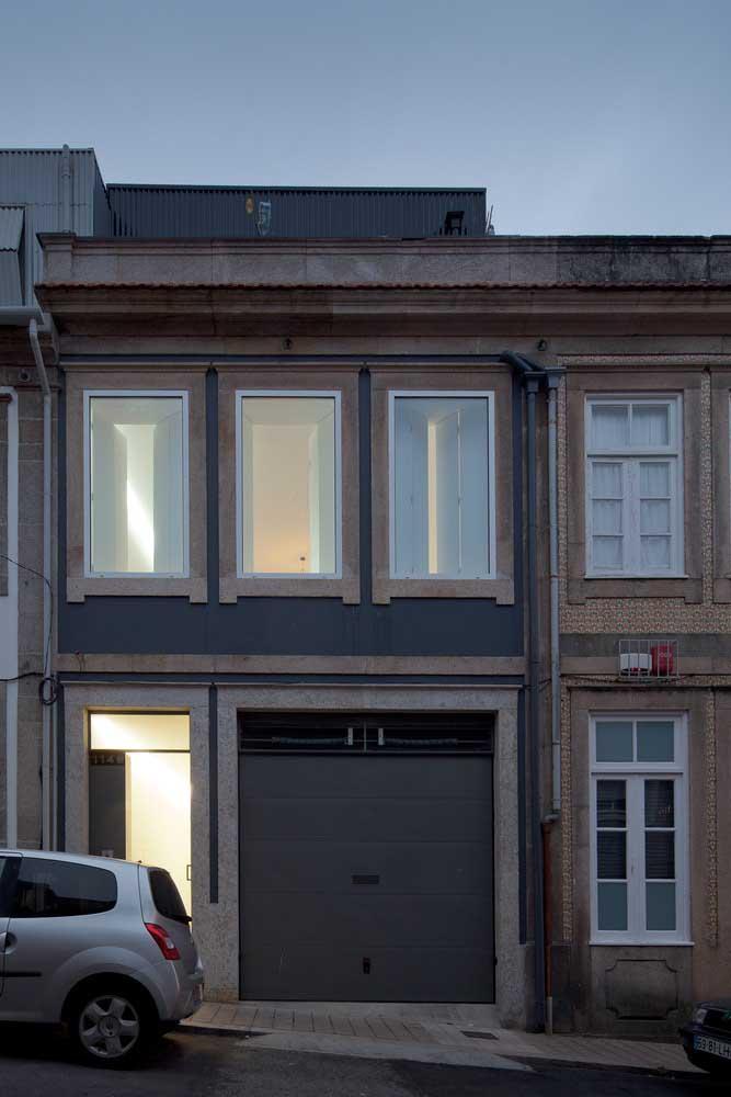 Portão de aço fechado para a casa sobrado; a abertura vazada superior permite a entrada de luz e ventilação para a garagem