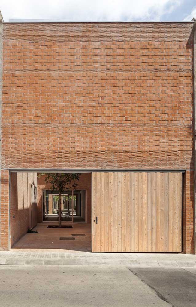 Quer uma fachada só de elementos naturais? Então invista em parede de tijolinhos e portão de madeira