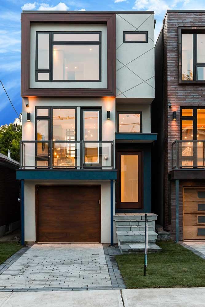 O primeiro pavimento dessa casa é dedicado à garagem fechada pelo portão de madeira