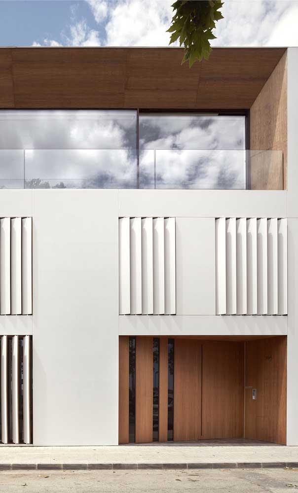 Nessa casa, o portão de madeira segue o mesmo padrão visual das paredes