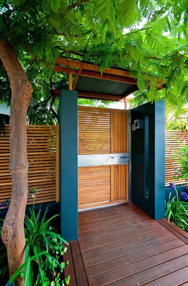 Portão de madeira e paredes azuis: uma combinação alegre e tropical