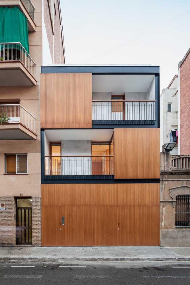 A madeira foi o material escolhido para a fachada dessa casa, presente nas paredes e no portão