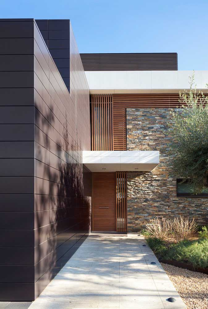 O portão de madeira completa a rusticidade das pedras naturais da parede