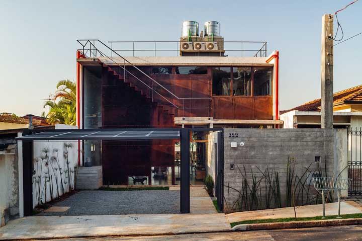 A casa de arquitetura moderna traz um mix de materiais em sua fachada, incluindo o aço corten nas paredes, o concreto aparente do muro e o aço galvanizado no portão