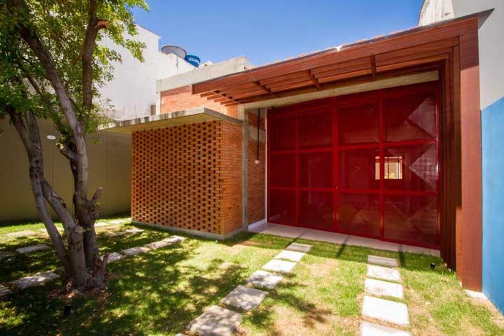 Combinação quente e aconchegante entre o portão vermelho e os tijolinhos aparentes