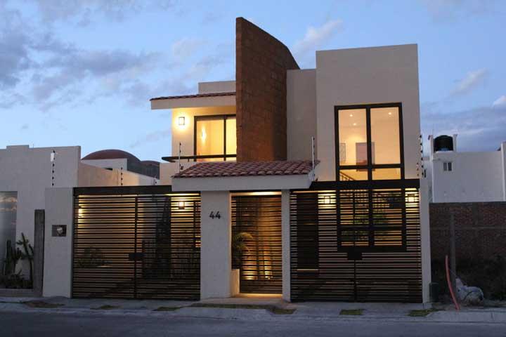 O portão preto valoriza a pintura branca da casa
