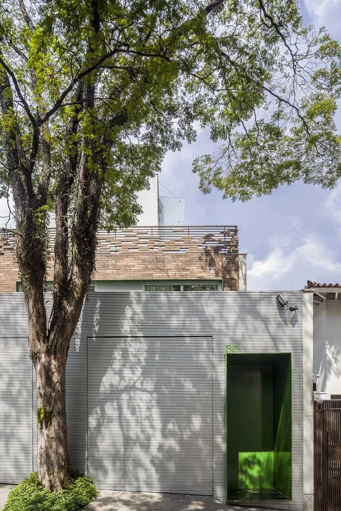 Dupla de portões brancos na fachada; para destacar a entrada social, um tom de verde marcante
