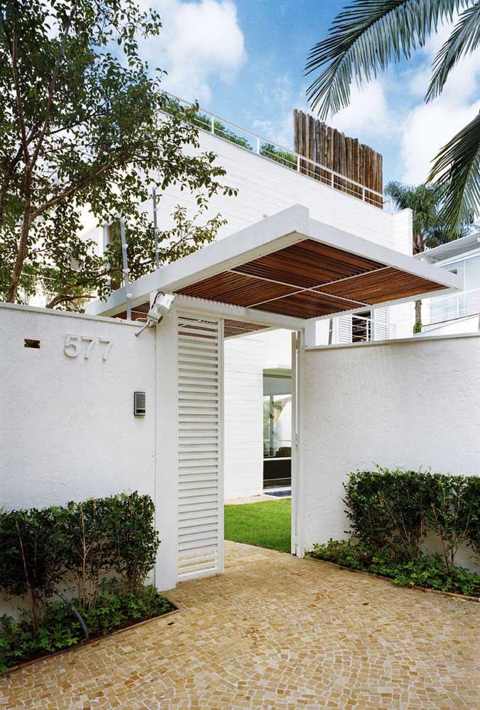 Muro branco e portão branco; o ponto de destaque fica por conta da cobertura de madeira