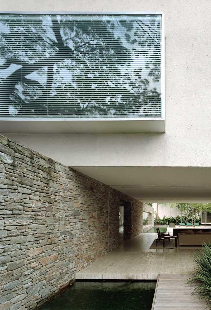 Contraste entre o rústico das pedras e a uniformidade da parede branca de alvenaria