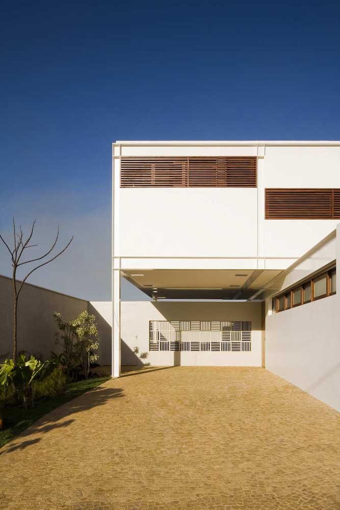 O muro alto dessa construção ganhou uma parte vazada que garante a visibilidade para o interior da casa